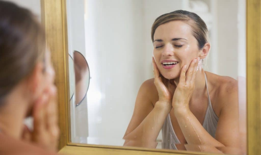 Young woman using Cerave to wash her face