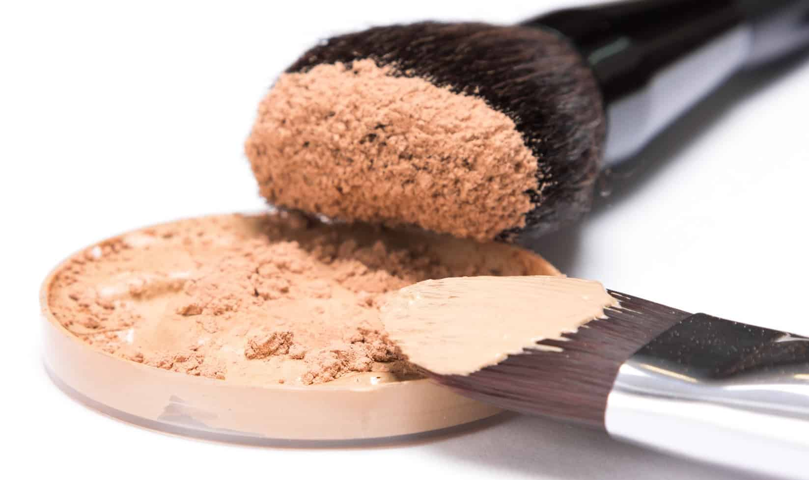 Round container filled with liquid foundation sprinkled with loose cosmetic powder and professional makeup brushes on white background. Side view, very shallow depth of field
