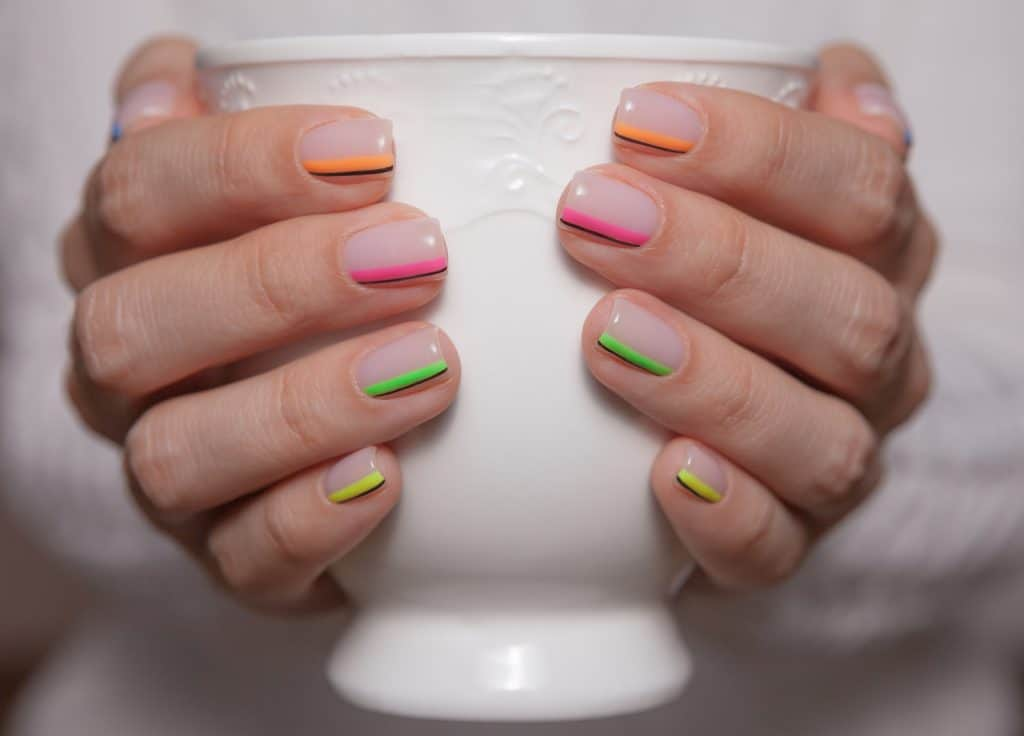 Close-up. Women's hands with a beautiful color manicure and white ceramic cup