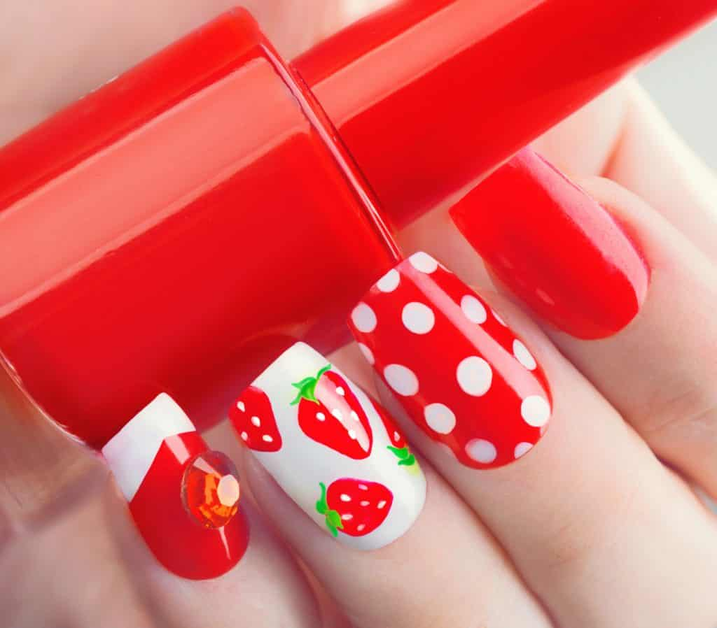 Nail art manicure. Summer style red manicure with strawberries and polka dots