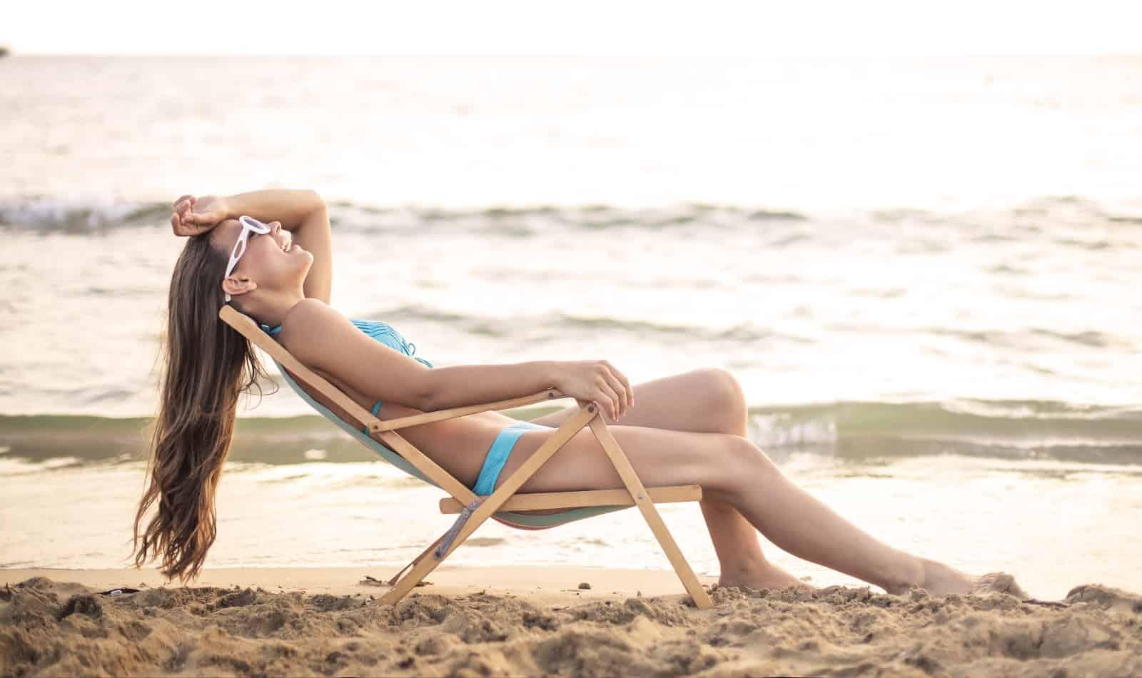 a woman in a blue bikini tanning on the beach