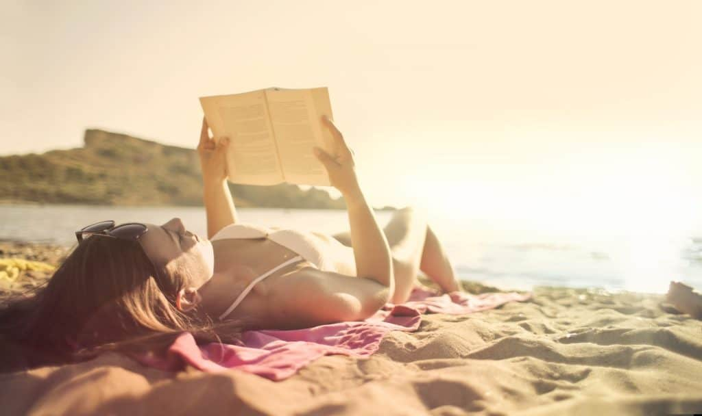 a lady reading book while tanning in the morning