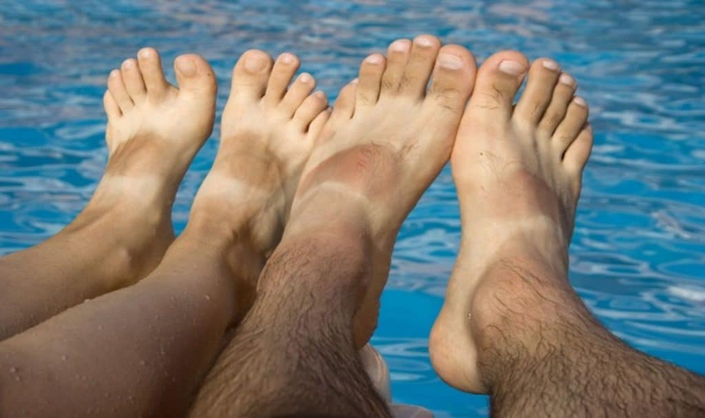 tanned bare feet of a man and a woman
