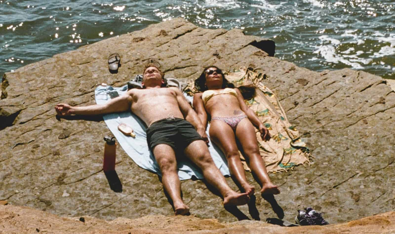 couple lying down on the cliff near the sea to get tan while it's cloudy