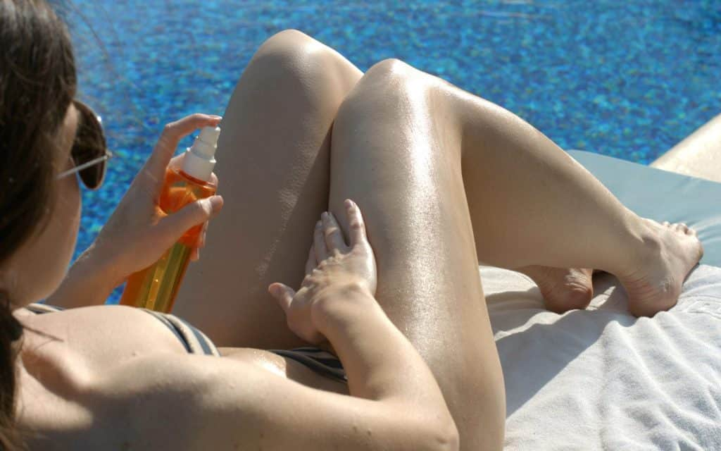 woman spraying tanning oil on her body for skin nourishment
