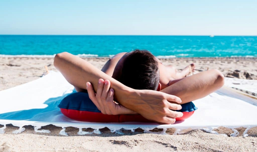 a man tanning in front of the beautiful beach