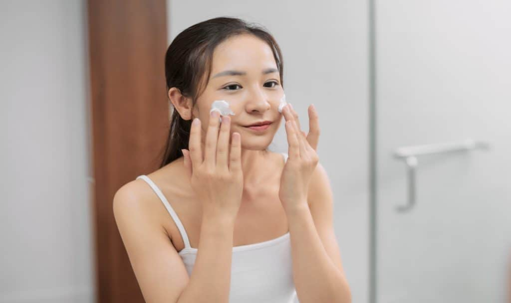 a happy beautiful korean double cleansing her face