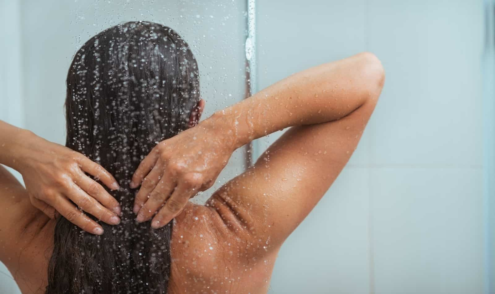 Woman washing long hair in shower after tanning