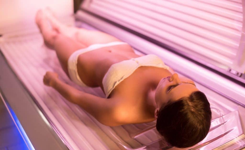 woman wearing a white bikini on a tanning bed