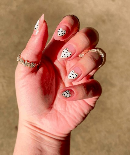 nude colored nails with white heart with polka dots