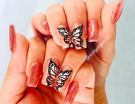 glittered nails with black outlined butterflies