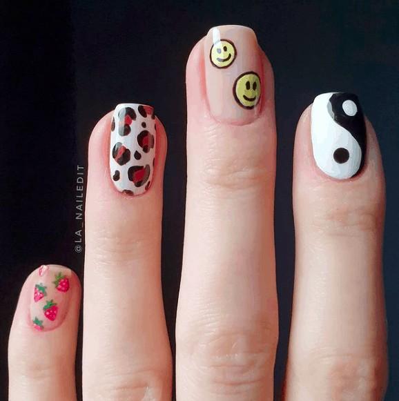 nail design with yellow circle smiling face, yin and yang, and strawberries