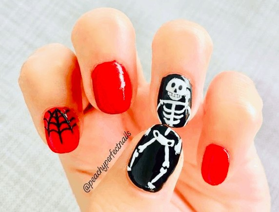red and black nails with skeleton smiley face