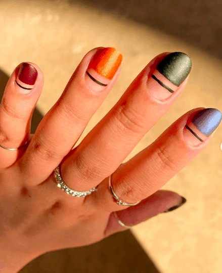 indie nail design consists of red, orange, green and blue with black lines below them