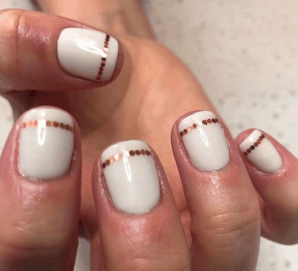 white indie nail design with gold dots lined below the tip of the nails