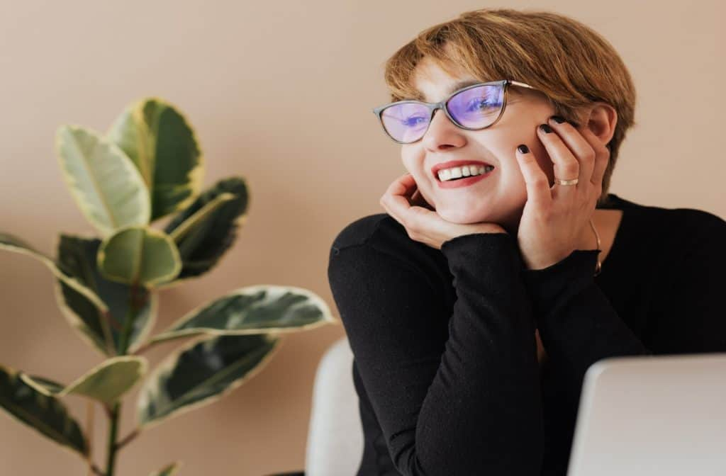 short hair lady with a reading glass smiling