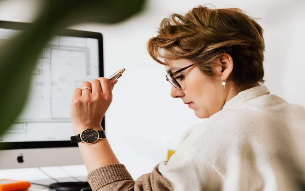 short hair working woman holding her pen in front of her computer