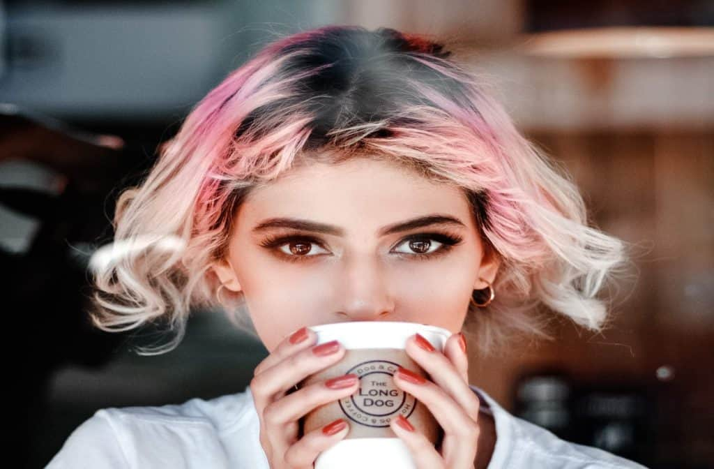 lady with a pink hair is drinking a coffee