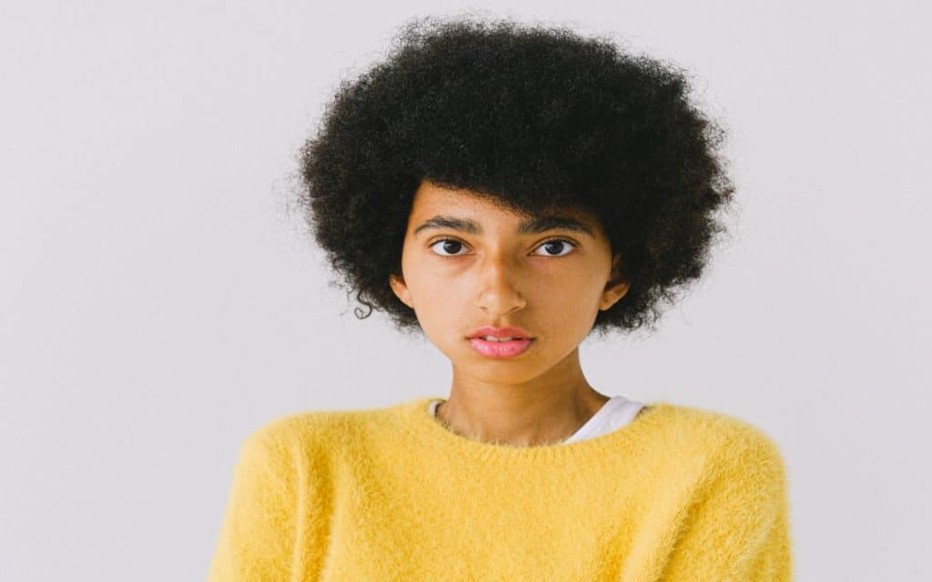 a girl in yellow sweater with very thick short hair