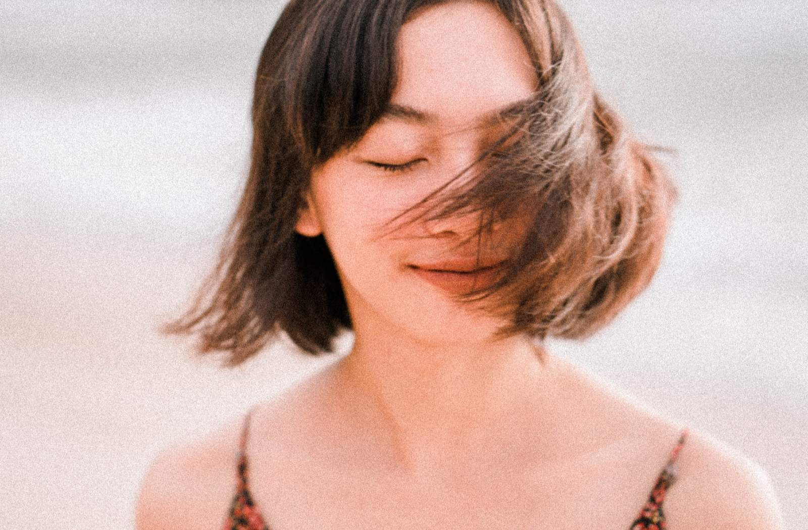a beautiful lady with short hair closing her eyes while feeling the fresh air