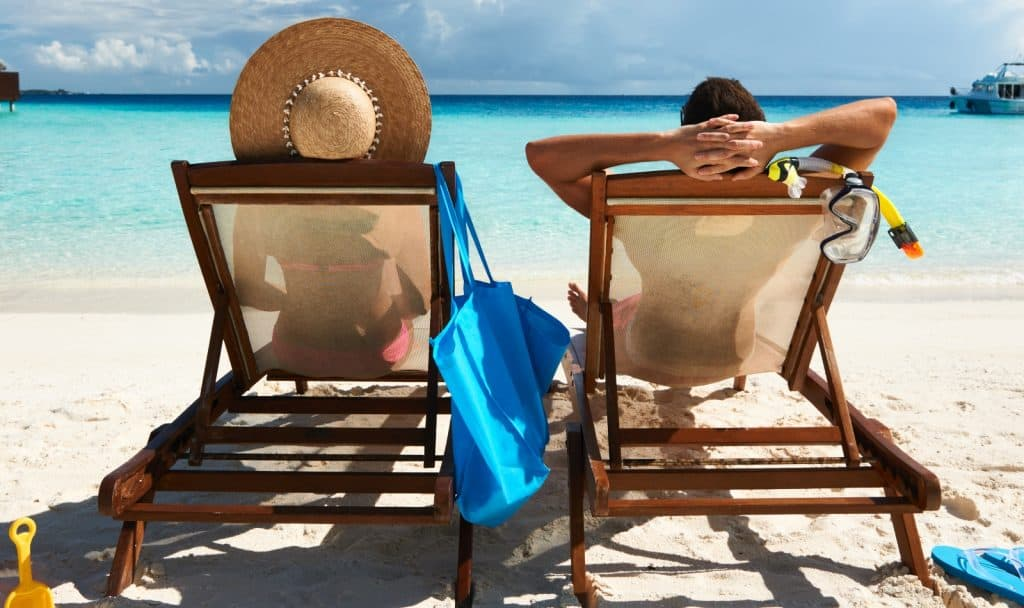 couple sitting on a beach chair while tanning