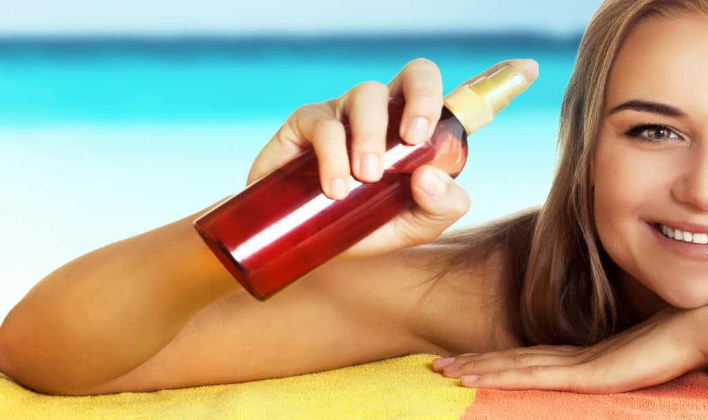nice smiling female lying down on the beach and holding in hand bottle with tanning oil