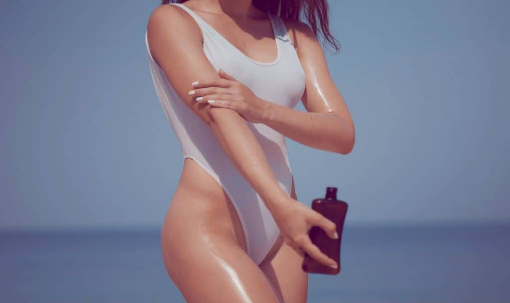 Beautiful girl in swimsuit diy tanning oil on body on the tropical sandy beach during summer
