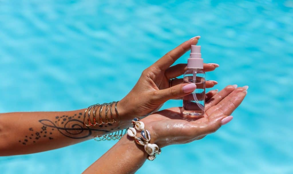 womans hands holding small bottle of tanning oil on background of blue swimming pool.