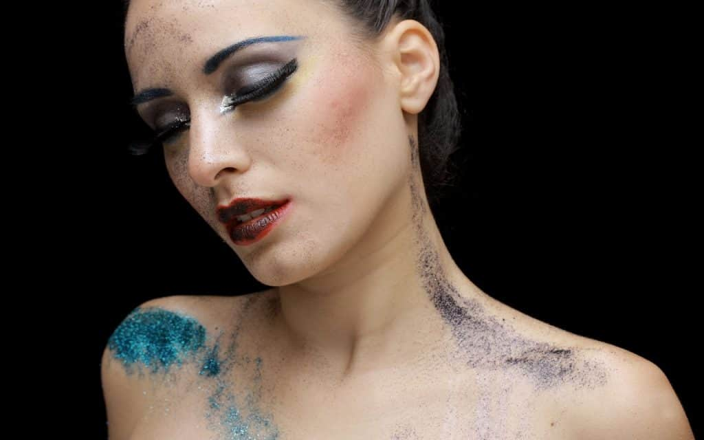 a lady with make up and paint on her face and body posing for a great makeup picture
