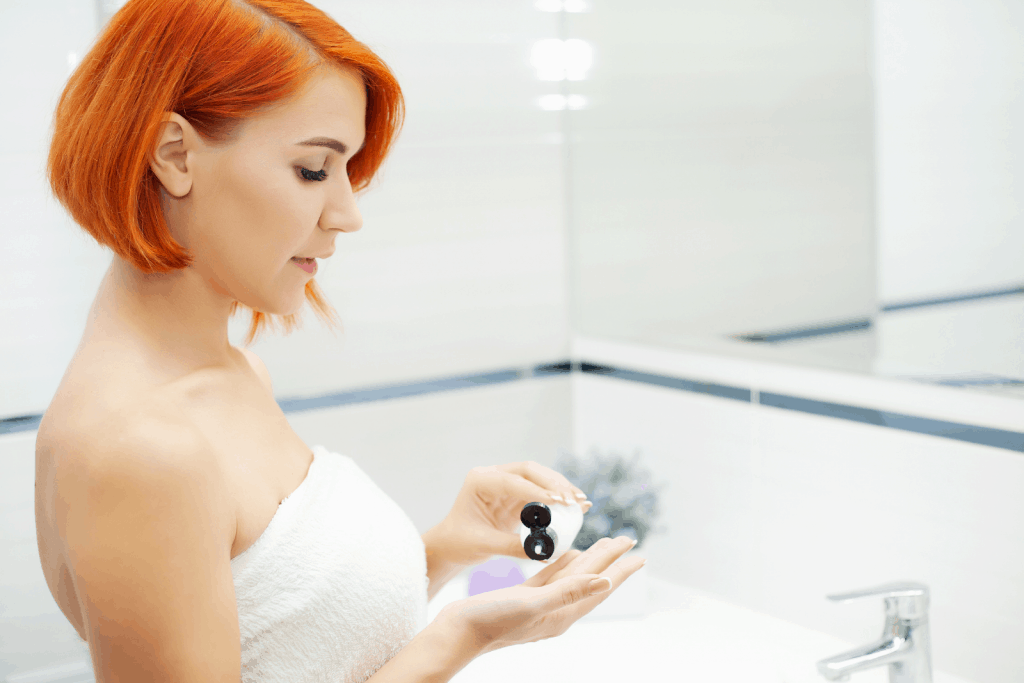 an orange-haired lady putting toner on her hands