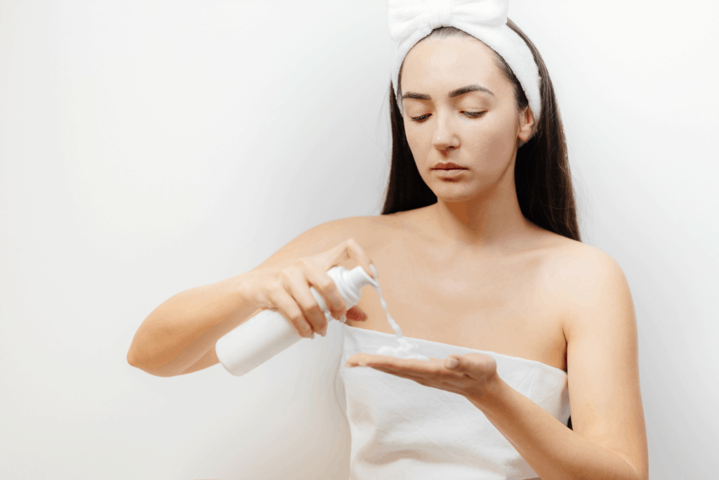 a lady in white putting facial foam cleanser on her hands to use for double cleansing