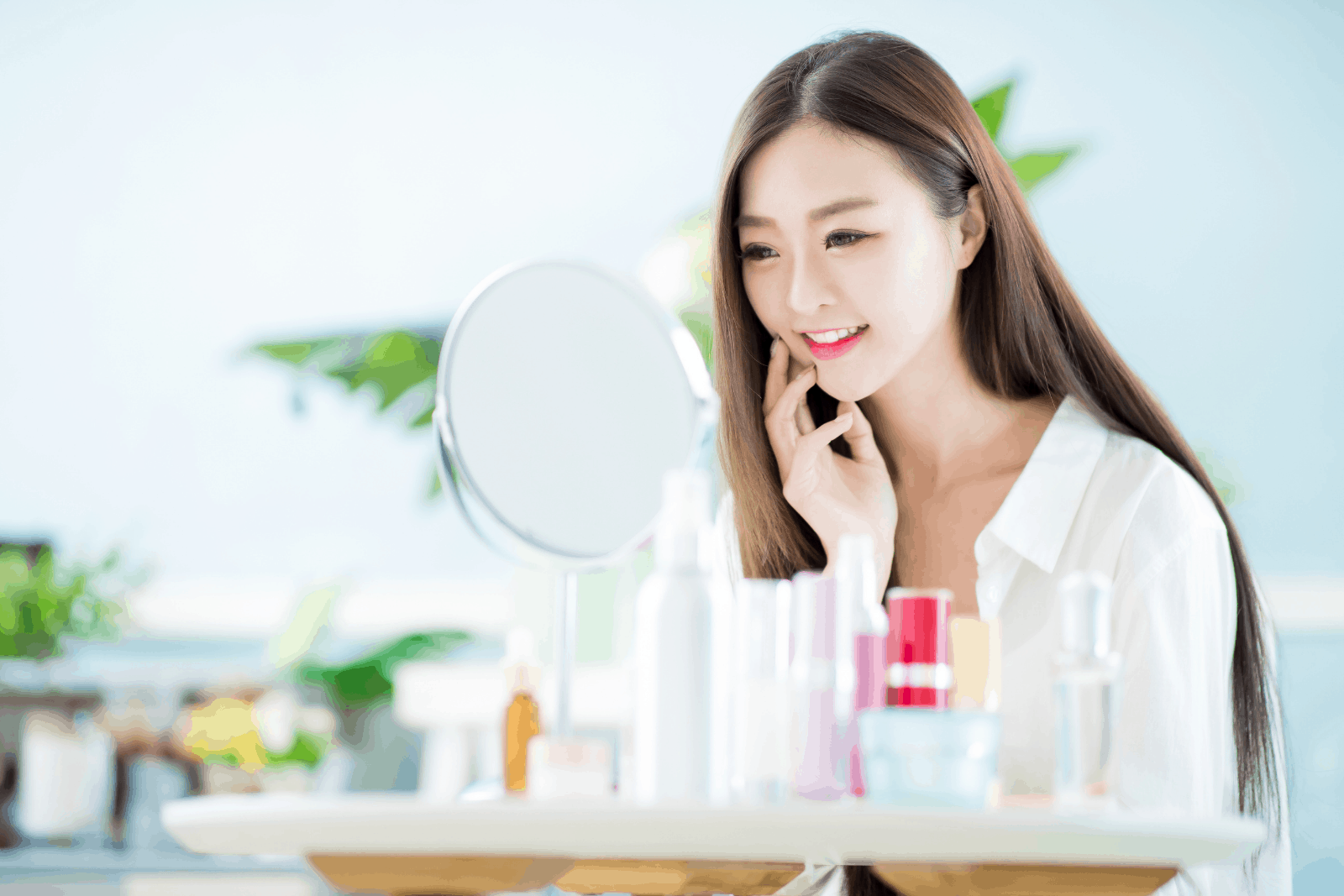 korean beauty hacks for flawless skin: a beautiful Korean lady beside a mirror in front of different skincare products