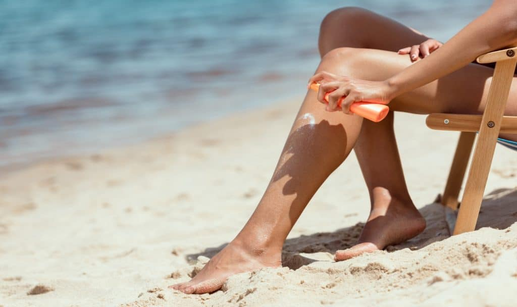 girl putting oil on her legs to protect her skin while tanning outside