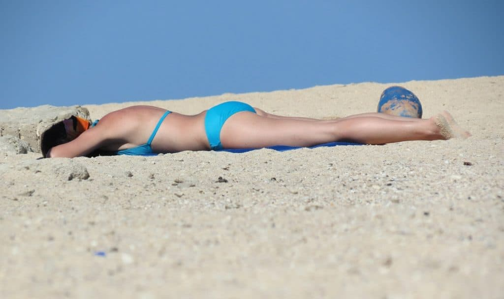 a lady in a blue bikini doing outdoor tanning on the beach