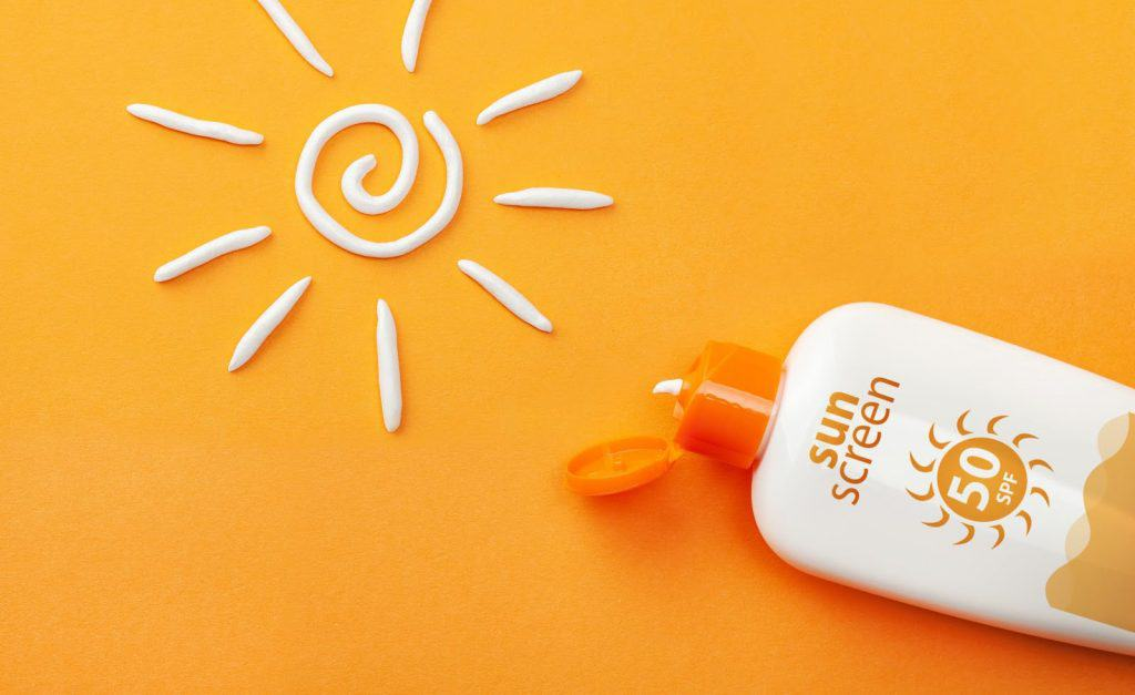 Sunscreen on orange background. Plastic bottle of sun protection and white sun-shaped cream.