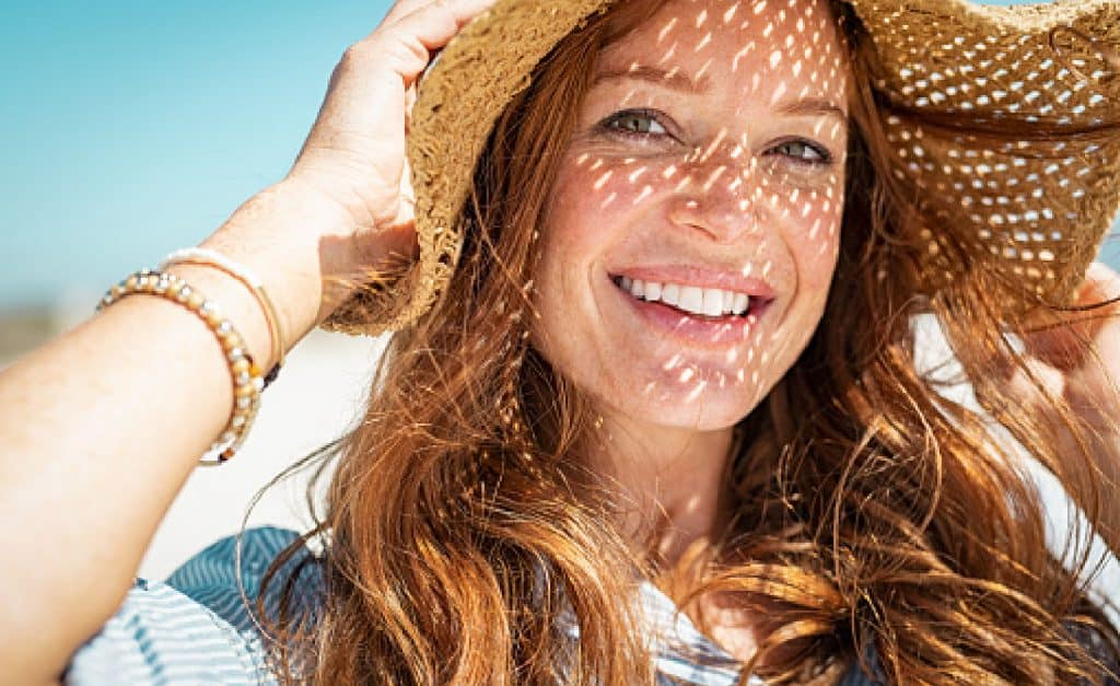 Portrait of beautiful woman wearing straw hat with large brim at beach and looking at camera.