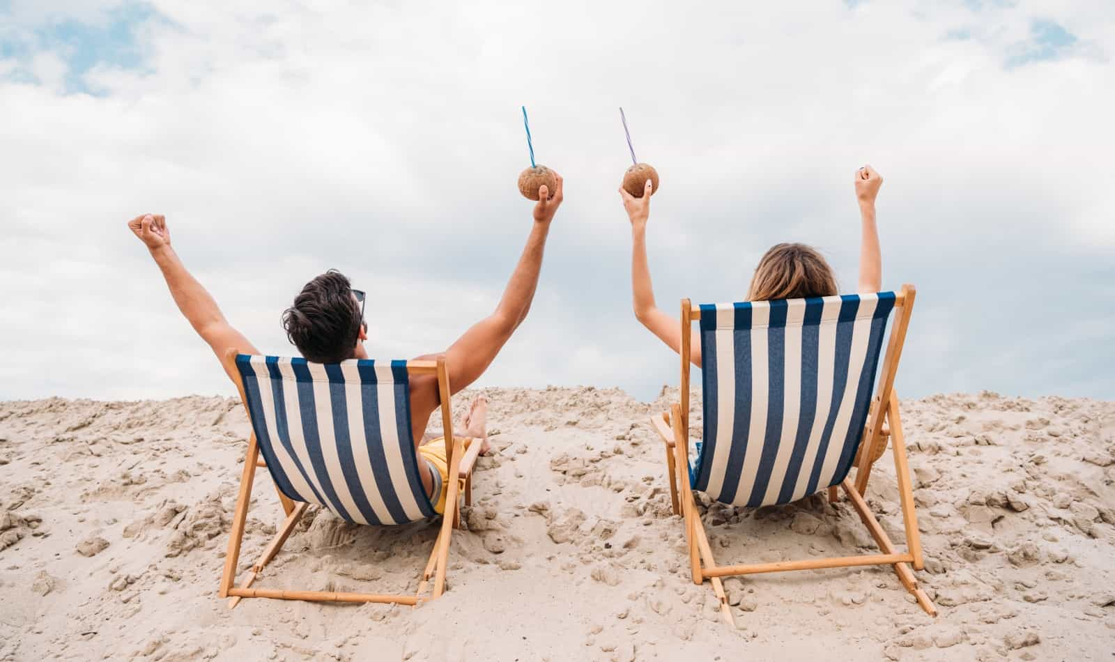 couple sitting on a beach chair and holding a coconut juice while tanning outside