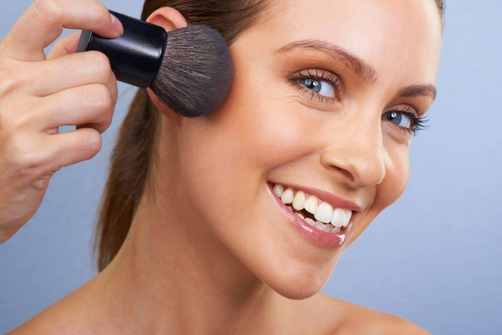 a smiling pretty lady showing how to apply bronzer to contour