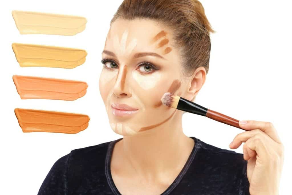 a gorgeous lady contouring her cheekbone using a blush brush
