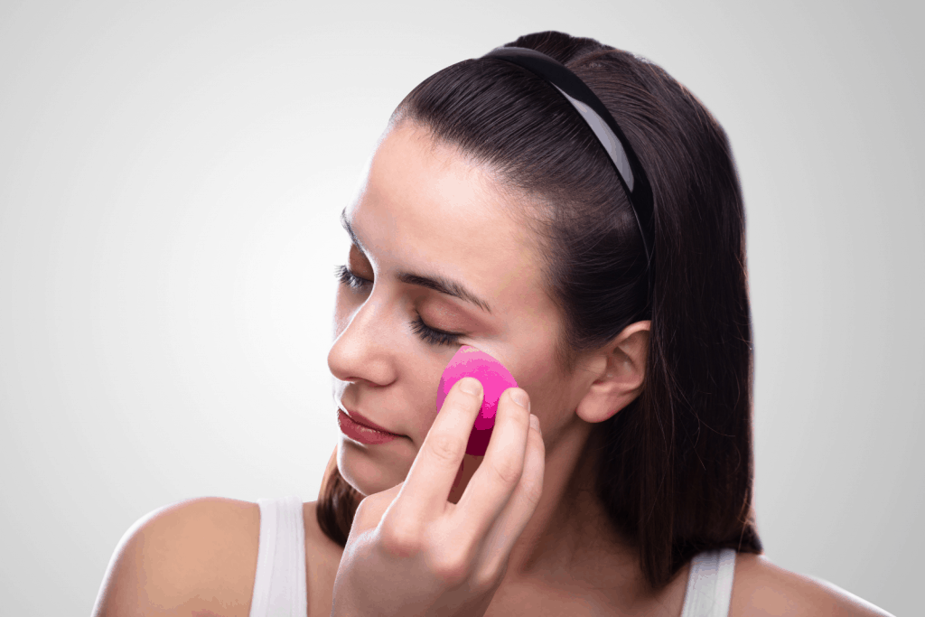 a lady demonstrating  how to use Real Techniques sponge pink miracle sponge