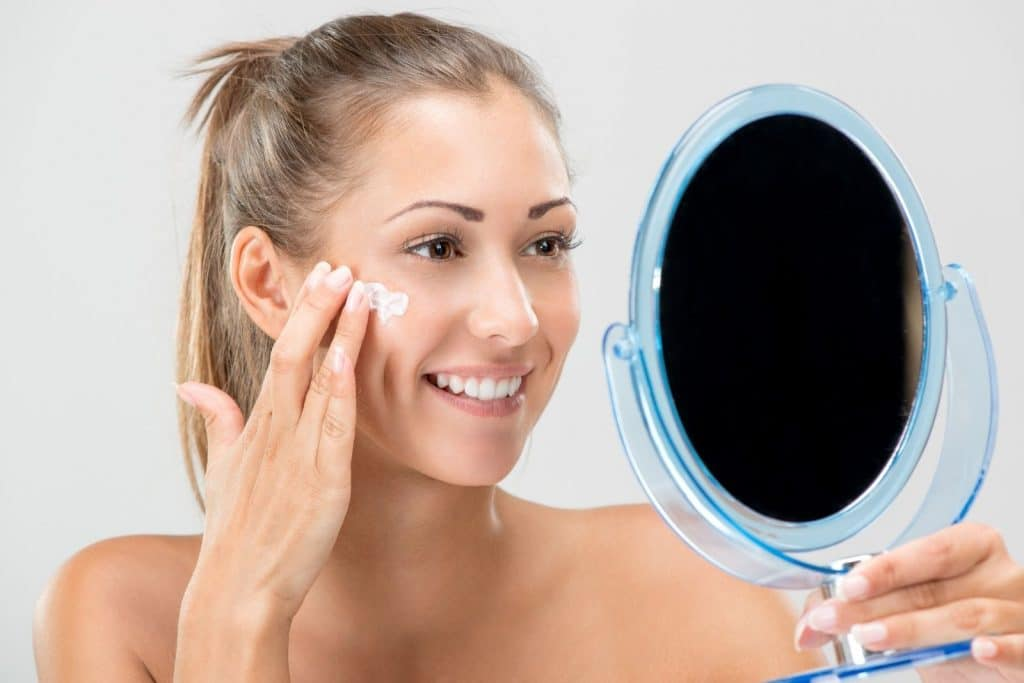 a smiling lady holding a mirror while putting a first aid beauty vegan cream