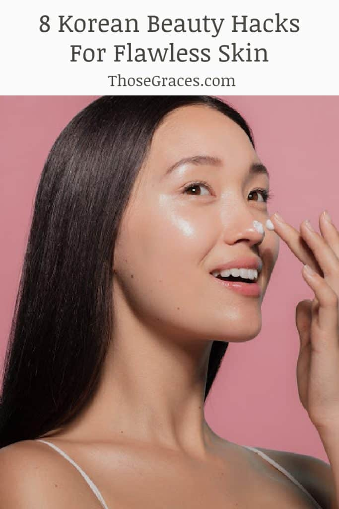 Korean woman applying skincare cream to her nose with a pink background behind her.