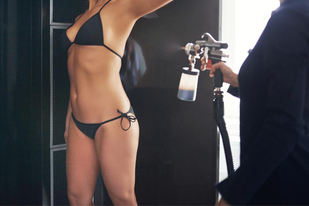 a woman in black putting spray tan on a slim body