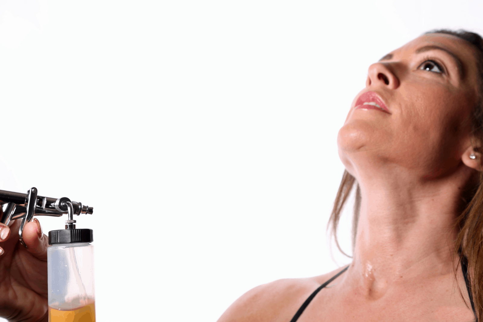 a lady putting a spray tan on her neck