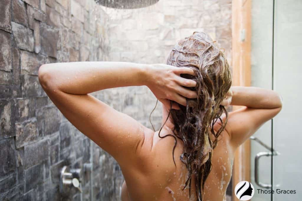 a lady massaging her hair using a shampoo