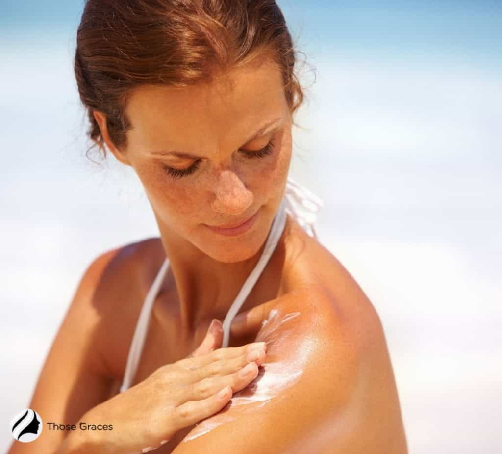 brown-haired lady applying a tanning lotion on her shoulders
