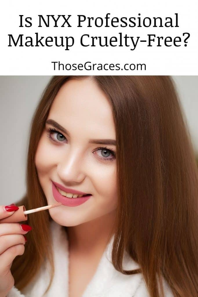 a pretty lady with blue eyes facing in front of the camera while putting a nude pink lipstick
