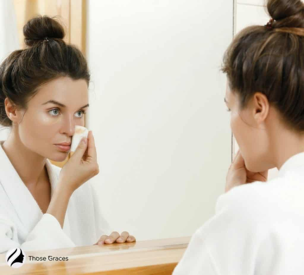 a girl removing her makeup in front of a wide mirror