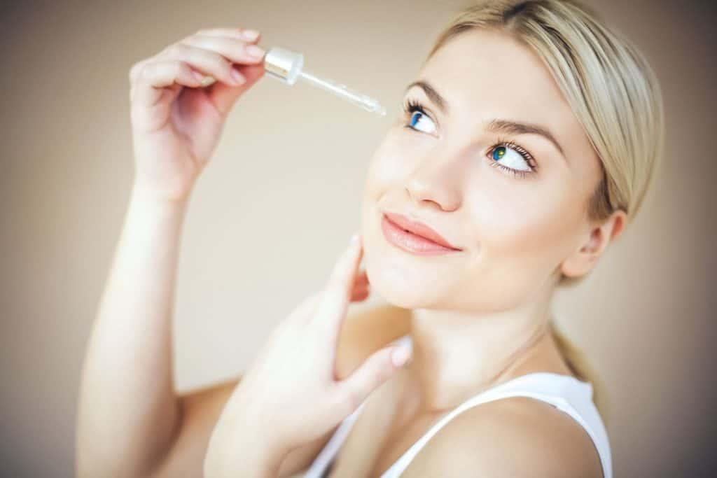 blonde woman putting eyelash serum on her lashes