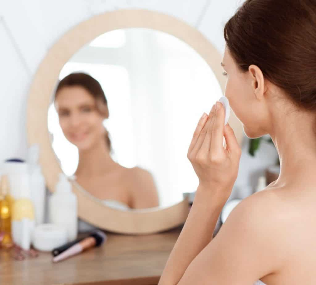lady using the best Korean essence while facing the wooden framed mirror